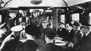 Signature de l'armistice entre la France et l'Allemagne, le 22 juin 1940 à Compiègne (Oise), en présence d'Adolf Hitler (assis à gauche) et du général CharlesHuntziger (à droite), qui préside la délégation française. (PHOTOSVINTAGES / AFP)