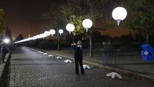 """Une passante photographie les ballons de la """"frontière de la lumière"""", qui matérialise le mur de Berlin, le 7 novembre 2014. (© PAWEL KOPCZYNSKI / REUTERS / X00616)"""