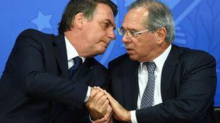 Le président brésilien Jair Bolsonaro (à gauche) et son ministre de l'Economie Paulo Guedes, le 16 juillet 2019 à Brasilia. (EVARISTO SA / AFP)
