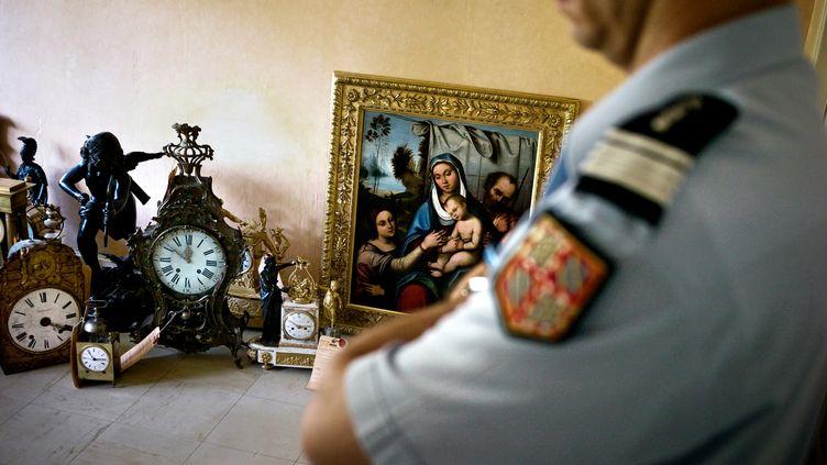 Un gendarme examine des objets d'art volés,le 23 Juin 2009 à Dijon. (JEFF PACHOUD / AFP)