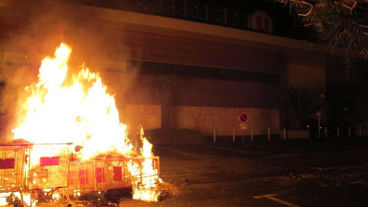 Des éleveurs de porcs incendient des chariots sur le parking d'une grande surface, dans la nuit du jeudi 11 au vendredi 12 juin 2015, à Lanvallay (Côtes-d'Armor). (F. MAGNENOU / FRANCE TV INFO)