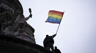 Un drapeau arc-en-ciel, symbole du mouvement LGBTQ+ et de la lutte contre l'homophobie, en haut de la statue de la République, à Paris, le 31 janvier 2021. (LOU OSRA / HANS LUCAS / AFP)