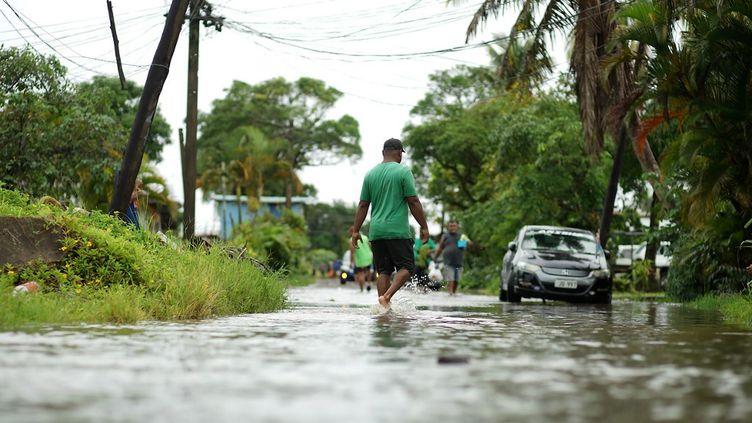 Des résidents pataugent dans les rues inondées de Suva, la capitale des Fidji, le 16 décembre 2020. (LEON LORD / AFP)