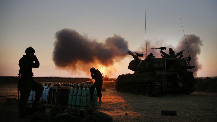 Un char de l'armée isréalienne ouvrant le feu sur la bande de Gaza, le 21 juillet 2014. (MENAHEM KAHANA / AFP)