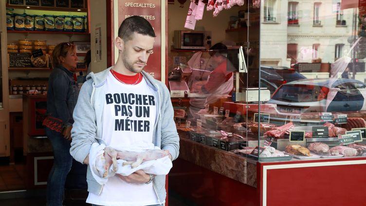 Un membre du mouvement Boucherie Abolition porte un cochonnet mort devant une boucherie, à Paris, le 22 septembre 2018. (JACQUES DEMARTHON / AFP)