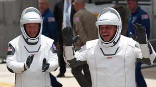 Les astronautes de la NasaBob Behnken (droite) and Doug Hurley (gauche) déambulent dans le centre spatial Kennedy, en Floride (Etats-Unis), le 27 mai 2020, avant de décoller pour la Station spatiale internationaleà bord d'une capsule conçue par le groupe privé SpaceX. (JOE RAEDLE / GETTY IMAGES NORTH AMERICA / AFP)