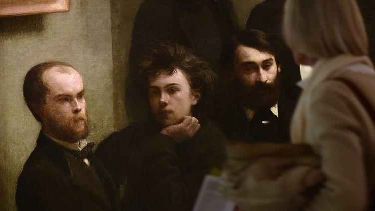 """Paul Verlaine, Arthur Rimbaud (à gauche et au centre), dépeints en 1872 par Henri Fantin-Latour dans le tableau """"Coin de table"""" (photo prise lors d'une exposition sur Verlaine en octobre 2015 à Bruxelles) (EMMANUEL DUNAND / AFP)"""