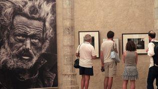 Des visiteurs regardent les photos de Don Mc Cullin lors de la 25e édition du Visa pour l'image, en 2013.  (RAYMOND ROIG / AFP)