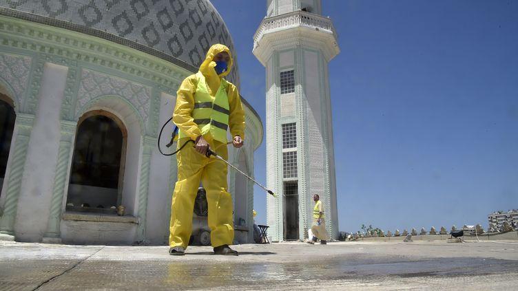 Un volontaire pulvérise une solution désinfectante sur le site de la mosquée Abou Hanifa d'Alger (Algérie), le 19 mai 2020. (RYAD KRAMDI / AFP)
