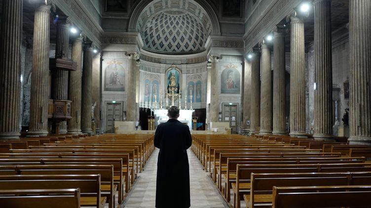 Un prêtre prie, seul dans son église, à Nice, le 27 mars 2020. (VALERY HACHE / AFP)