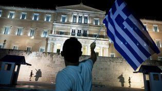 Un homme brandit un drapeau grec devant le Parlement à Athènes (Grèce), le 5 juillet 2015. (IAKOVOS HATZISTAVROU / AFP)