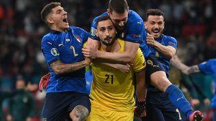 Gianluigi Donnarumma célébré par ses partenaires après la victoire de l'Italie aux tirs au but contre l'Angleterre en finale de l'Euro 2021. (LAURENCE GRIFFITHS / POOL)