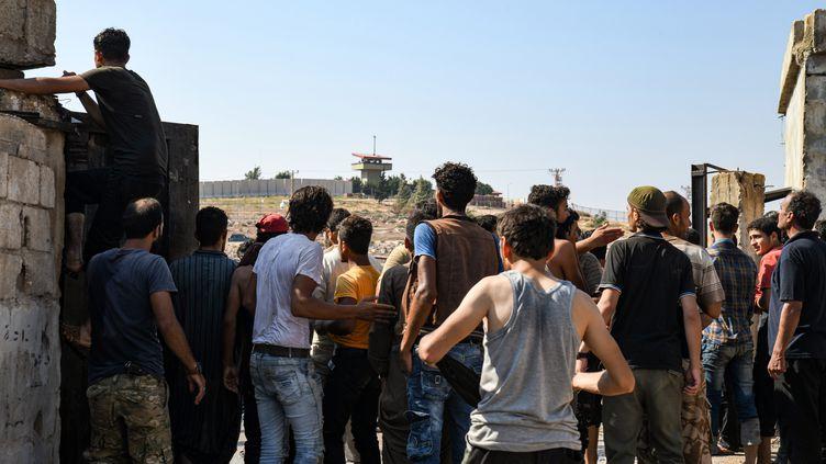 Des Syriens déplacés manifestent le 30 août 2019 près de la frontière turque dans la province d'Idleb, pour demander l'aide d'Ankara et arrêter l'offensive du régime de Damas dans la région. (RAMI AL SAYED / AFP)