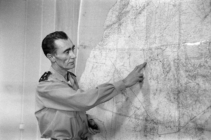 Le général JeanThiry indique aux journalistes français où se déroulera le premier essai nucléaire. Il montre sur la carte de l'Algérie la région de Reggane dans le Sahara algérien. Photo prise en Algérie le 27 décembre 1960. (- / AFP)