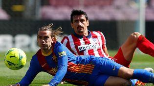 Antoine Griezmann, taclé ici par Stefan Savic, a passé une après-midi compliquée contre l'Atlético de Madrid, samedi 8 mai 2021. (ENRIC FONTCUBERTA / EFE)