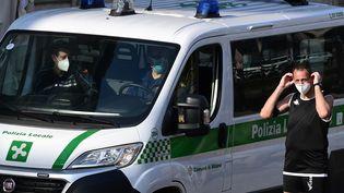 Un homme ajuste son masque à Milan (Italie), le 8 mai 2020. (MIGUEL MEDINA / AFP)