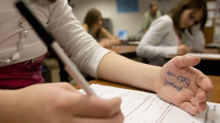 Un jeune fille regarde son antisèche lors d'une épreuve de mathématiques. (ANDY SACKS / PHOTOGRAPHER'S CHOICE / GETTY)