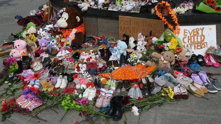 Des chaussures et des jouets pour enfants sont placés au pied de la flamme du centenaire pour rendre au hommage aux enfants autochtones dont les restes de 215 corps ont été retrouvés dans un pensionnat de Colombie-Britannique (1er juin 2021). (DAVE CHAN / AFP)