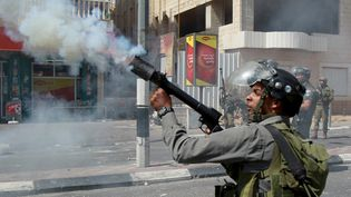 Un garde-frontière israélien tire du gaz lacrymogène contre des Palestiniens, le 21 septembre 2015 àBethléem, en Cisjordanie. (MUSA AL-SHAER / AFP)