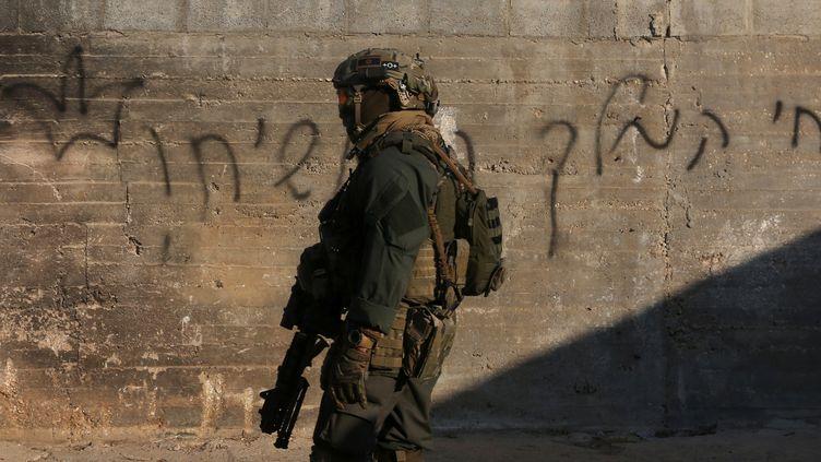 Un membre des forces de sécurité israéliennes devant la maison incendiée à Doma (Cisjordanie), le 31 juillet 2015. Un bébé palestinien y a été brûlé vif. (JAAFAR ASHTIYEH / AFP)