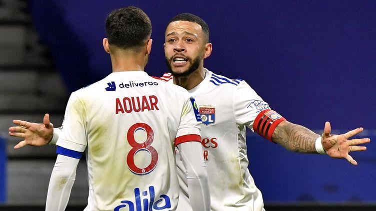 Houssem Aouar et Memphis Depay célébrant l'unique but de la rencontre face à Rennes lors de la 28e journée de Ligue 1.  (PHILIPPE DESMAZES / AFP)