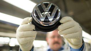 Un employé de Volkswagen tient un logo du constructeur allemand dans une usine de production à Wolfsburg (Allemagne). (JULIAN STRATENSCHULTE / DPA / AFP)