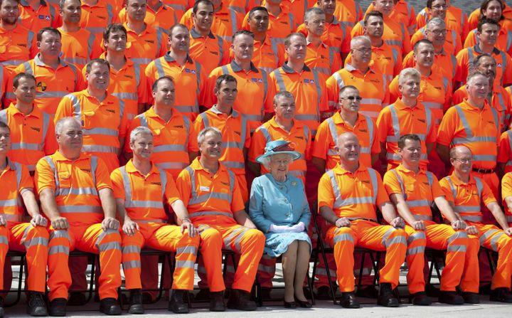 (Les rencontres avec des délégations de corps constitués ou de métiers constituent le quotidien de la reine. Ici, à Londres en 2014, avec des ouvriers à l'occasion de la réfection d'une station de métro. © REUTERS/POOL/Ben Gurr)