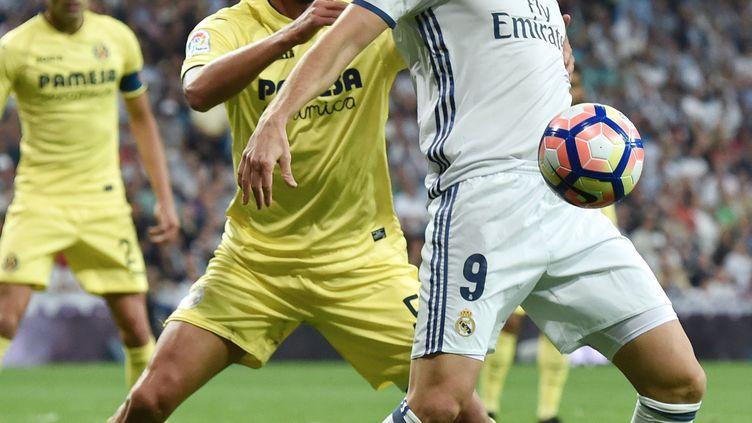 Karim Benzema, l'attaquant du Real Madrid, bien pris par le défenseur de Villarreal, Mateo Musacchio (GERARD JULIEN / AFP)