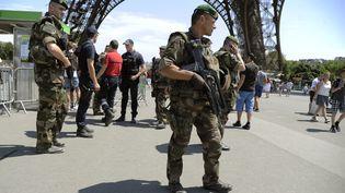 Des militaires patrouillent au pied de la Tour Eiffel à Paris, le 26 juin 2015. (THOMAS OLIVA / AFP)