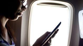 L'utilisation d'une tablette ou d'un téléphone pendant tout le vol sera progressivement autorisée dans les avions américains voyageant aux Etats-Unis et à l'étranger. (JENEIL S / FLICKR OPEN / GETTY IMAGES)