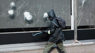 """Un manifestant tente de détruire une vitrine sur l'avenue des Champs-Elysées à l'aide d'un pied-de-biche, le samedi 16 mars 2019 en marge d'une manifestation de """"gilets jaunes"""". (KARINE PIERRE / HANS LUCAS / AFP)"""