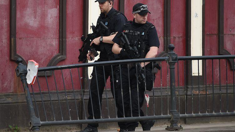 Despoliciers patrouillent, le mardi 23 mai 2017, aux abords de la station Victoria à Manchester, au lendemain de l'attentat qui a fait au moins 22morts. (OLI SCARFF / AFP)