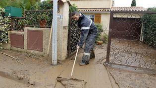 Un pompier nettoie l'entrée d'une maison inondée à La Londe-les-Maures (Var), le 28 novembre 2014. (MAXPPP)