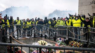 """Des """"gilets jaunes"""" entourés par les forces de l'ordre, samedi 1er décembre 2018 à Paris. (KARINE PIERRE / AFP)"""