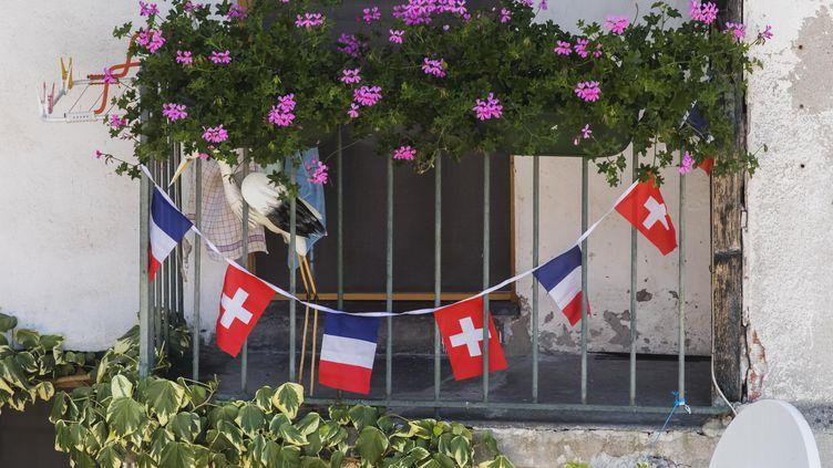 Des drapeaux français et suisse accrochés à un balcon deSaint-Gingolph, un village transfrontalier situé au bord du Lac Léman, en Haute-Savoie. (VINCENT ISORE / MAXPPP)