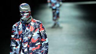 A partir d'un même imprimé camouflage en bleu, rouge et blanc, que la marque Moncler décline sur tous les supports (poncho, cape, costume, manteau...) et tous les tissus (laine, fausse fourrure, molleton...), l'homme à la marque au coq tricolore, cagoule sur la tête, se moque des apparences.  (GIUSEPPE CACACE / AFP)