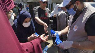 Distribution de masques près d'Alger le 21 mai dernier (RYAD KRAMDI / AFP)