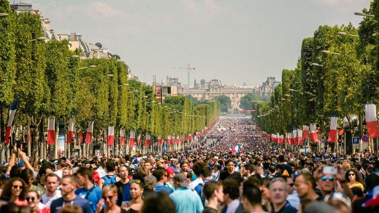 Des supporters sur les Champs-Elysées pour la parade des Bleus, le 16 juillet 2018 à Paris. (SIMON GUILLEMIN / HANS LUCAS / AFP)