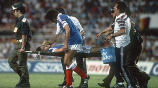 Le défenseur Patrick Battiston est évacué après avoir été heurté de plein fouet par le gardien allemand Harald Schumacher, le 8 juillet 1982 à Séville (Espagne). (STAFF / AFP)