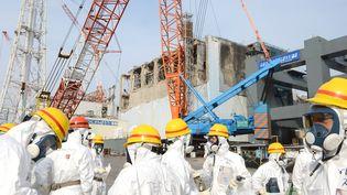 """Des """"nettoyeurs"""" rassemblés près du réacteur n°4 de la centrale de Fukushima (Japon), le 7 mars 2013. (MASNARI GENKO / YOMIURI / AFP)"""