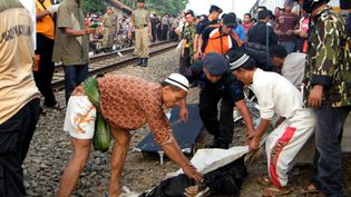 Des policiers indonésiens évacuent le corps d'une victime, le 2 octobre 2010. (AFP PHOTO / SLAMET MARTOYO)