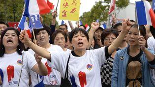 Des manifestants d'origine chinoise défilent à Paris, le 21 août 2016,pour réclamer la findes violences répétées à leur encontre après la mort d'un couturier chinois agressé à Aubervilliers. (BERTRAND GUAY / AFP)