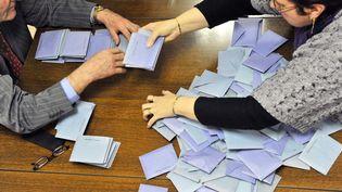 Des personnes participent au dépouillement d'une élection à Jumeaux (Puy-de-Dôme), le 14 mars 2010. (THIERRY ZOCCOLAN / AFP)
