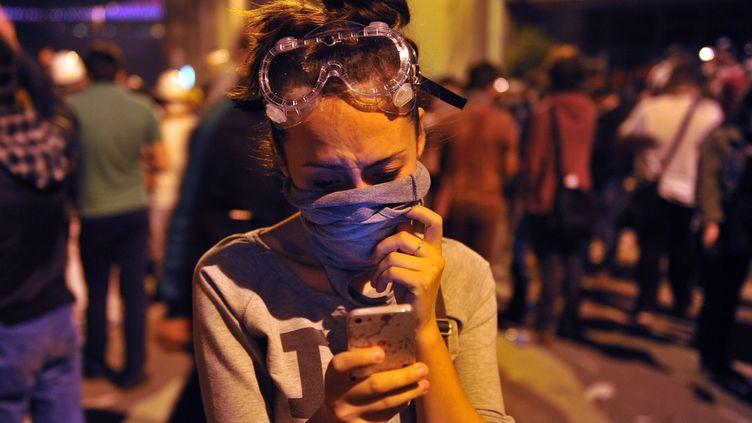 Une jeune femme tape sur son portable en marge d'un rassemblement sur la place Taksim à Istanbul, le 3 juin 2013. (OZAN KOSE / AFP)