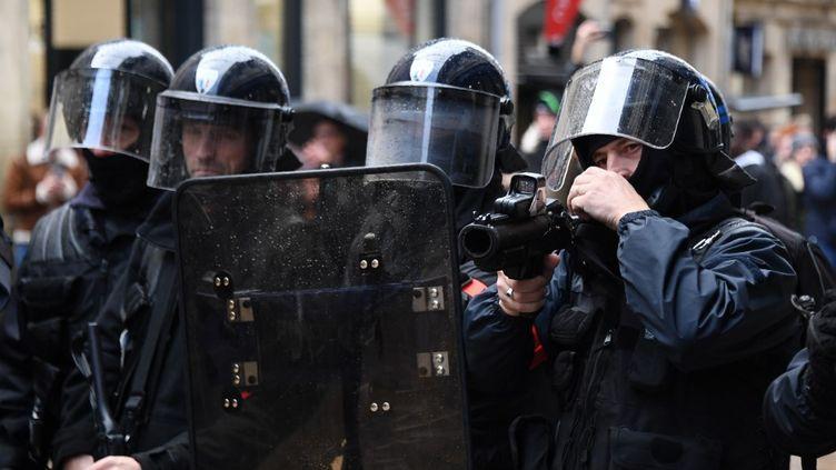 """Un groupe de policiers, dont l'un pointe un lanceur de balles de défense(LBD) lors d'une manifestation des """"gilets jaunes"""" à Bordeaux (Gironde), le 16 novembre 2019. (MEHDI FEDOUACH / AFP)"""