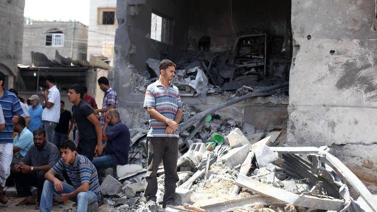 Des Palestiniens dans les décombres de la maison du chef de la police du Hamas, bombardé par l'armée israélienne, le 13 juillet 2014. (MAJDI FATHI / NURPHOTO / AFP)