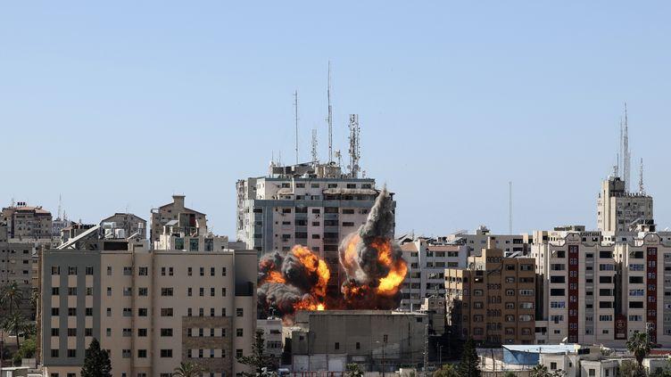 Un immeuble abritrant des médias internationaux est détruit par une frappe israélienne, le 15 mai 2021, à Gaza. (MAHMUD HAMS / AFP / AP)