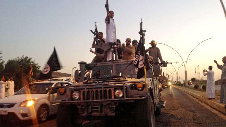 Des jihadistes paradent dans une rue de Mossoul, en Irak, le 23 juin 2014. ( AP / SIPA )