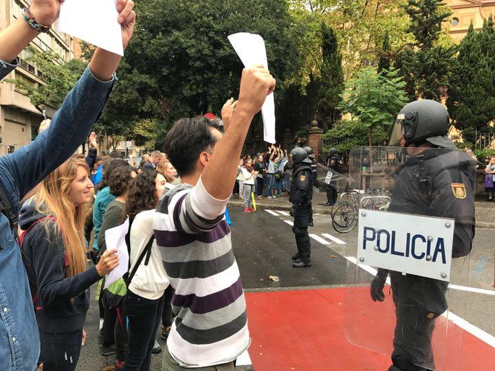 Des habitants brandissent des blletins de vote devant des policiers, à Barcelone, dimanche 1er octobre. (ROBIN / PRUDENT)