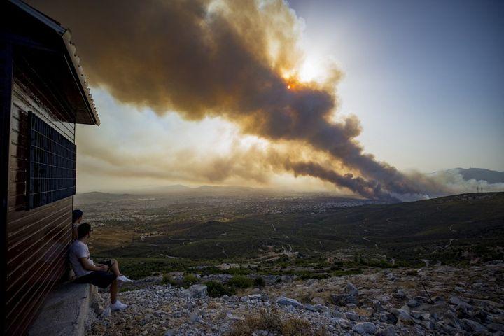 Pria menyaksikan api di Varibobi, Yunani, 3 Agustus 2021 (ALEX GRYMANIS / SOOC / AFP)